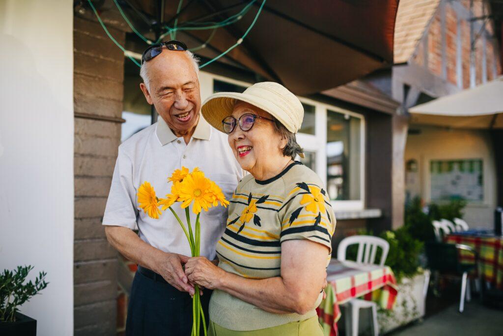 Elderly couple holding flowers