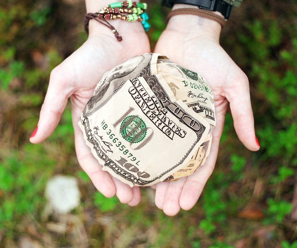hands holding a ball made of cash