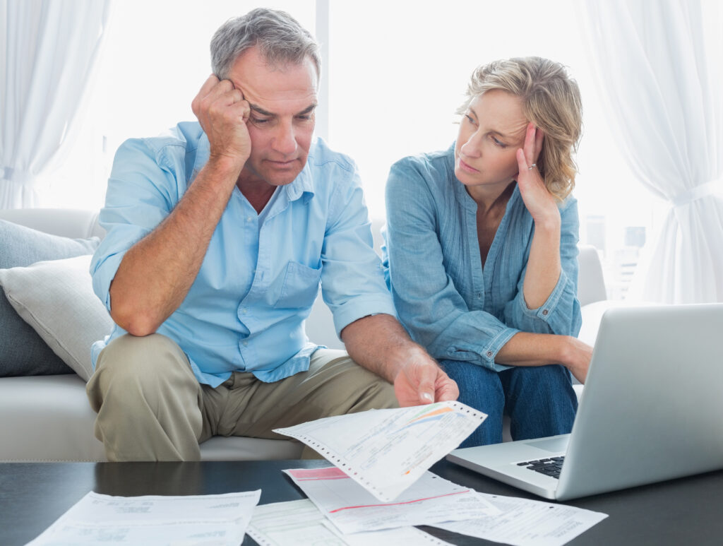 Worried couple paying bills in front of laptop